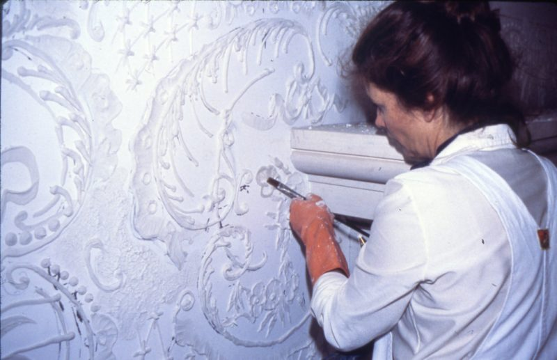 Artist applying plaster designs on a wall