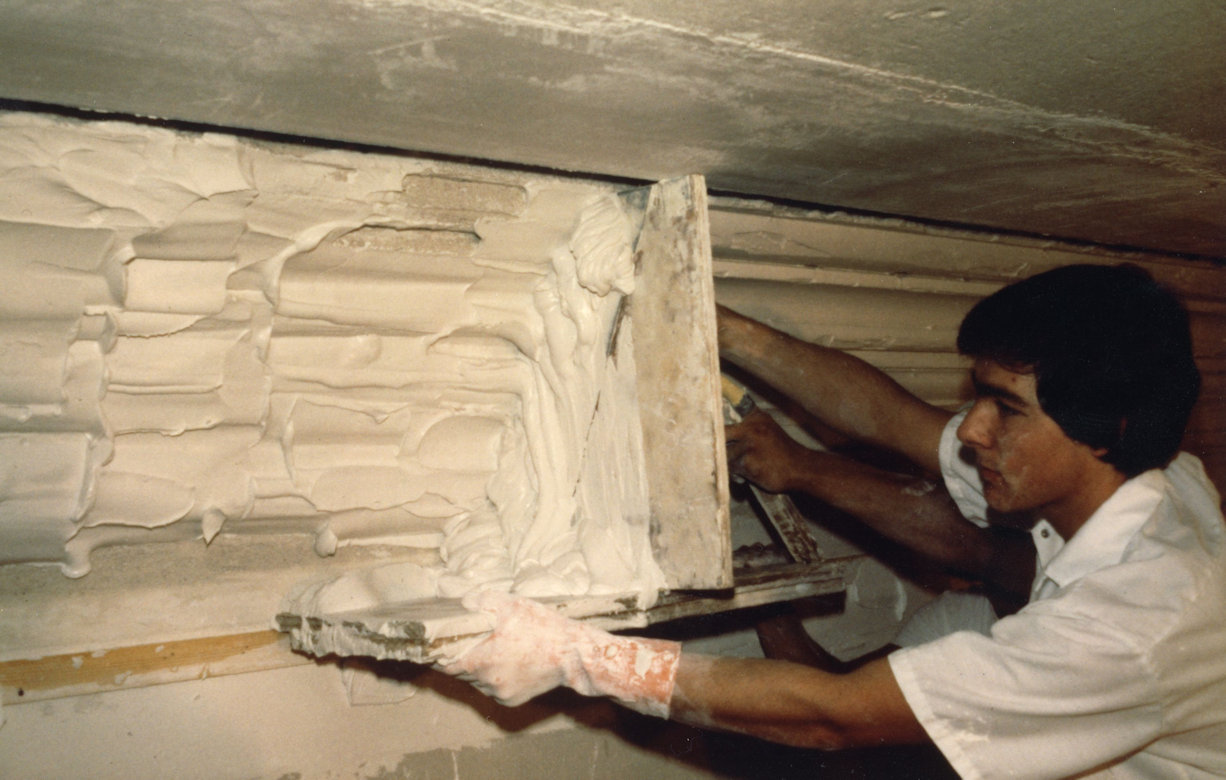 Artist using template for decorative plasterwork molding