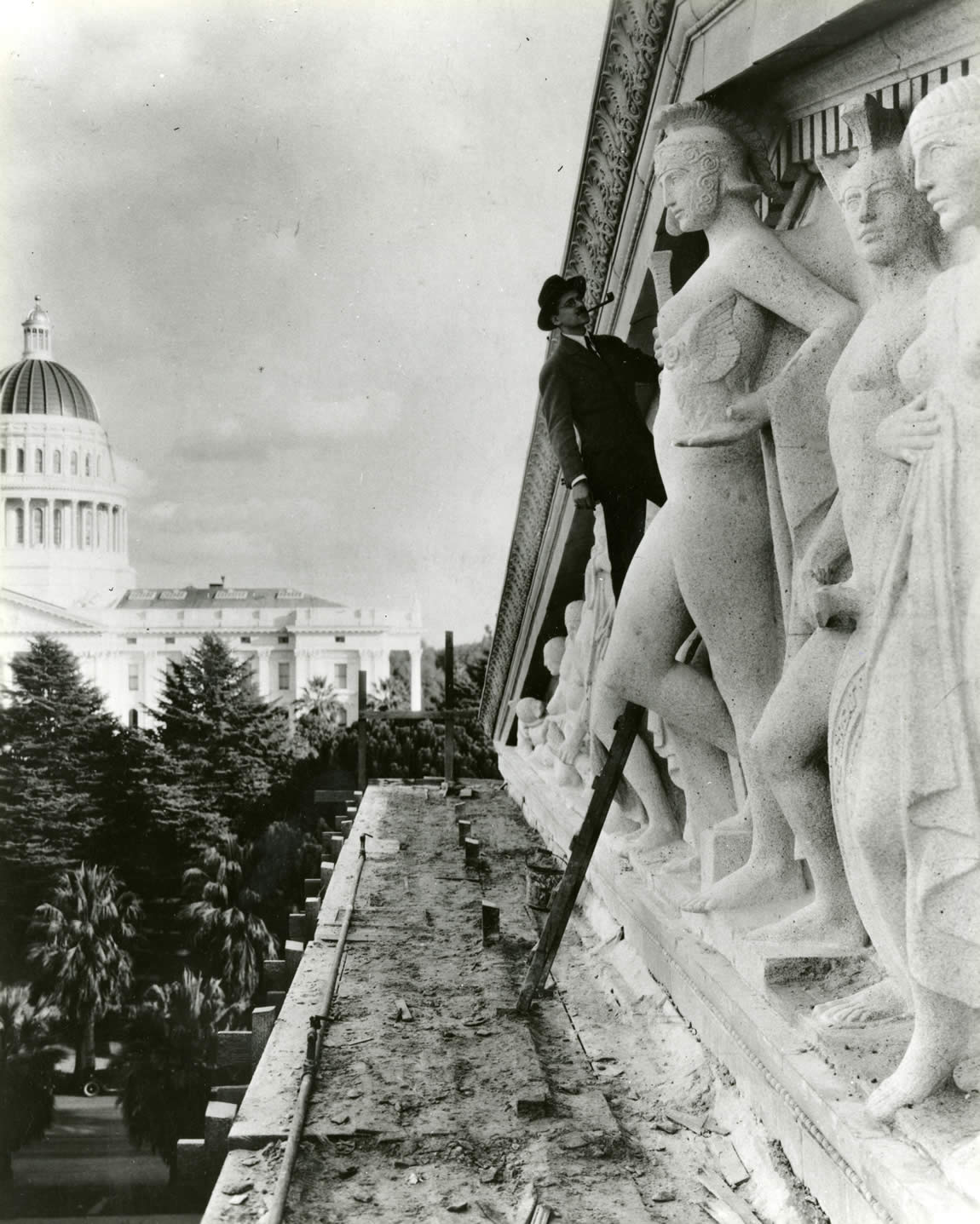 Sculptor Edward Field Sanford, Jr. examining his work on the pediment of the Library and Courts Building, late 1920s