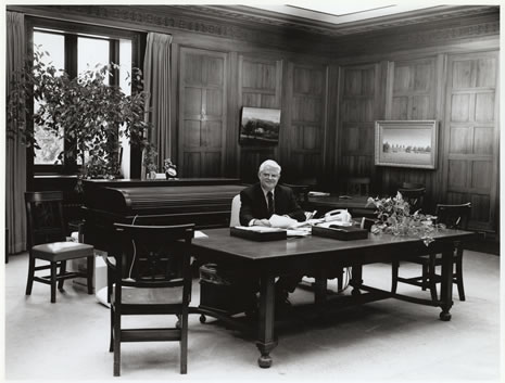 Photograph of Gary E. Strong, the eighteenth State Librarian, seated at his desk in the State Librarian's office.