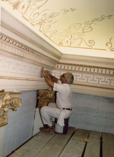Artist applying slow drying adhesive to Assembly Chamber ornamentation