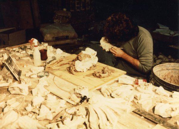 Restoration specialist examining original plaster fragments
