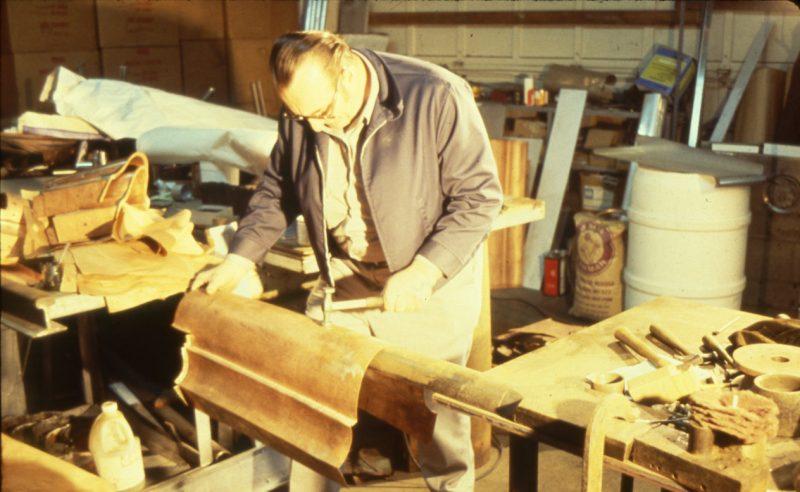 Restoration worker shaping duplicates of the original metal dome shingles