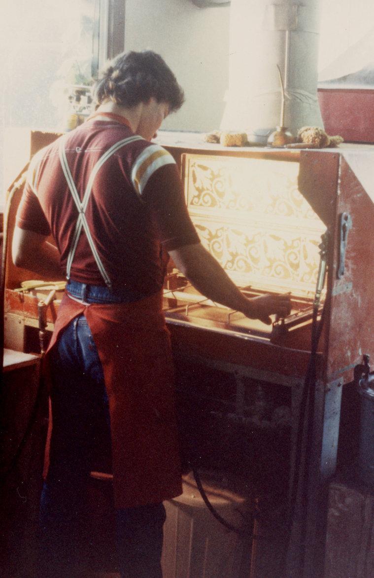 Tile worker using screens to paint Eureka tiles