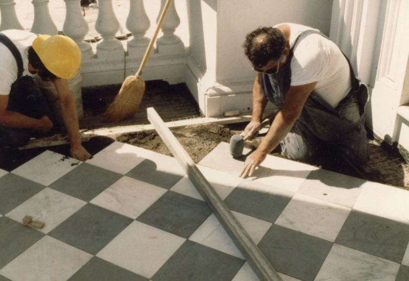 Workers laying marble tiles on the West Portico